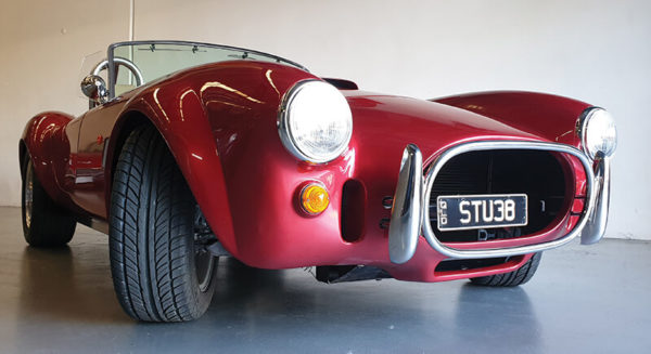 front view of red ac cobra parked inside Australian garage